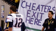 Oct 18, 2015; Indianapolis, IN, USA; New England Patriots quarterback Tom Brady (12) walks past a sign referencing Deflategate at halftime during the NFL game against the Indianapolis Colts at Lucas Oil Stadium. Mandatory Credit: Brian Spurlock-USA TODAY Sports